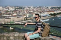 Tourist in der Sonnenbrille mit Rucksack und Kamera steht auf dem Hintergrund von Budapest still Stockbild