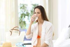 Tourist, der trinkbares Leitungswasser in einem Hotelzimmer trinkt stockbild