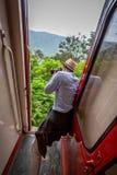Tourist, der von der offenen Zugtür genommen auf Nanu Oya-Bahnreise in Sri Lanka fotografiert stockfotos