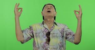 Tourist des älteren Mannes im bunten Hemd, das Meditation tut Stattlicher alter Mann stock video footage
