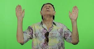 Tourist des älteren Mannes im bunten Hemd, das Meditation tut Stattlicher alter Mann stock video