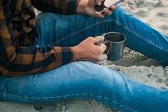 Tourist des jungen Mannes mit seinem Morgentasse kaffee, der zum Meerblick schaut Stockbilder