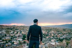 Tourist des jungen Mannes von einem Höhepunkt, der den Sonnenuntergang über der Stadt von Goreme in Cappadocia in der Türkei und  lizenzfreies stockbild