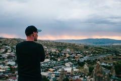 Tourist des jungen Mannes von einem Höhepunkt, der den Sonnenuntergang über der Stadt von Goreme in Cappadocia in der Türkei und  stockbilder