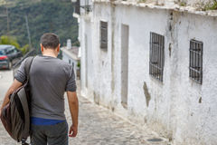 A tourist descends a street in a small village Stock Image