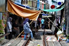 Bangkok Train Market sellers. A tourist desitnation and novelty, sellers often move their goods whilst the train runs through the centre of the market royalty free stock images