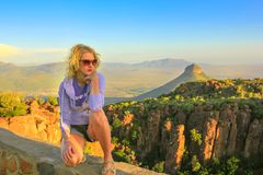 Tourist at Desolation Valley. Young tourist sitting on the rocks at sunset after trekking at Valley of Desolation near Graaff-Reinet, South Africa. Blonde woman royalty free stock images
