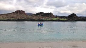 Tourist dinghy motoring between Chinese Hat and Santiago islands, Galapagos National Park, Ecuador stock video
