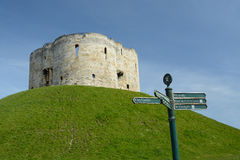 A tourist direction signpost by Cliffords's tower a stone monument in York UK Royalty Free Stock Photography