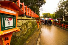 Tourist down the path passing the street lanterns spring time japan royalty free stock image