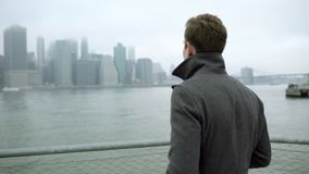 Tourist drinking coffee while walking near Hudson river with Manhattan on background. Attractive young male tourist drinking coffee while walking near Hudson stock video footage