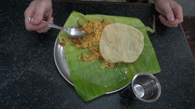 Tourist eating vegetarian rice with tomato on banana leaf in south India Stock Photos