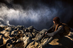 Tourist at the edge of waterfall. Tourist is sitting on the stone at the edge of waterfall Stock Photography