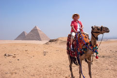 Tourist, Egypt Pyramid, Travel, Vacation. A retired elderly woman is on holiday in Egypt. The lady is riding a camel in the desert in the shadow of the Great Stock Photography