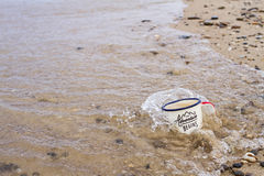 Tourist enamel mug with water on the sandy beach of Lake Baikal in summer during the tide is covered with a wave. Tourist enamel mug with water on the sandy Stock Image