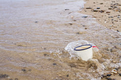 Tourist enamel mug with water on the sandy beach of Lake Baikal in summer during the tide is covered with a wave. Tourist enamel mug with water on the sandy Stock Photography