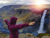 Tourist enjoying dramatic view of high waterfall in Iceland. Bright flare on the background. Iceland is truly a remarkable place for wonders of nature hunters stock photos