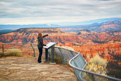 Tourist enjoying scenic view in Bryce Canyon National Park, Utah, USA. Tourist enjoying scenic view of the Amphitheater from Inspiration Point, Bryce Canyon Stock Images