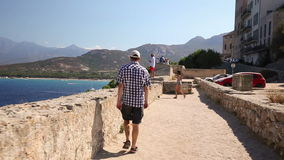 Tourist enjoying the stunning view of the beach and mountains in Calvi, Corsica, Europe. Young man walking and enjoying the stunning view of Calvi old town stock video