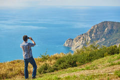 Tourist enjoying the view of Cinque Terre coast, Italy Royalty Free Stock Image