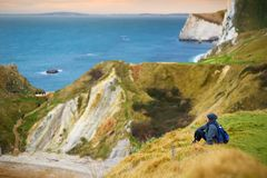 Tourist enjoying view of Man O`War Cove on the Dorset coast in southern England, between the headlands of Durdle Door to the west. And Man O War Head to the Stock Image
