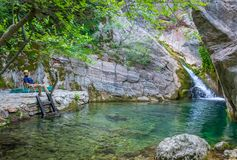 The tourist enjoys views of the small picturesque waterfall. royalty free stock photo