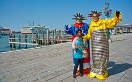 Tourist with entertainers. Happy, laughing tourist with entertainers both wearing masks on the quayside in Venice stock images
