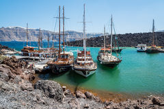 Tourist excoursion boats at small port on volcano of Santorini island Royalty Free Stock Images