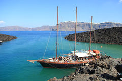 Tourist excursion boat at small port on volcano of Santorini Stock Photos