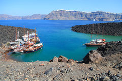 Tourist excursion boats at small port on volcano of Santorini Royalty Free Stock Images