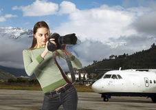 Tourist in exotic country. Attractive girl-photographer on landing strip Stock Photo