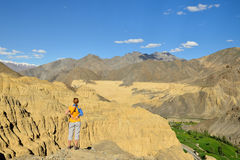 Tourist during expedition in the mountains Ladakh is admiring the beautiful Karakorum panorama in the vicinity of the Lamayuru tow Royalty Free Stock Image