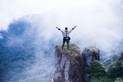Tourist explorer man at top of mountain cloud background. Tourist explorer man standing on top of rock mountain in rain forest park with beautiful cloud Stock Images