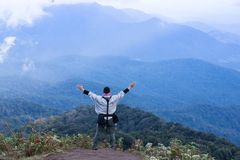Tourist explorer man at top of mountain cloud background. Tourist explorer man standing on top of mountain in rain forest park with beautiful cloud background Royalty Free Stock Photography