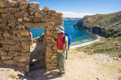 Tourist exploring the ancient mysterious Inca labyrinth-like settlement, called Chinkana, on the Island of the Sun, Titicaca Lake,. Bolivia. Travel adventures Royalty Free Stock Photos