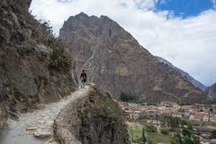 Tourist exploring the Inca Trails and the archaeological site at Ollantaytambo, Sacred Valley, travel destination in Cusco region,. Peru. Vacations and royalty free stock photography