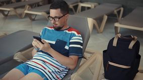 tourist-eyeglasses-hanging-out-pool-lounge-chair-texting-chatting-sitting-onlive-cellphone-casual-guy-129306651.jpg