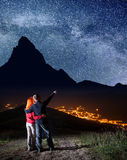 Tourist family - man and woman hugging. Male hiker showing on stars and Milky way in beautiful starry sky at night Royalty Free Stock Photos