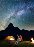 Tourist family - man and woman looking at the shines starry sky at night. Couple hikers sitting near camp and campfire stock images