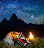 Tourist family - man and woman looking to the shines starry sky and Milky way in the camping at night near campfire. Tourist family - men and women looking to Stock Images