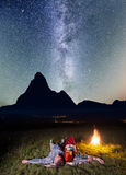 Tourist family - man and woman lying near the campfire under incredibly beautiful starry sky and Milky way at night Stock Photos