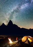Tourist family sitting face to face in front tent near campfire under shines starry sky at night. Long exposure Royalty Free Stock Photography