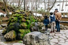 Tourist family with stone and moss at Fukidashi Park, was made at the area that natural water from Mt.Yotei in Hokkaido, Japan.  Royalty Free Stock Photo
