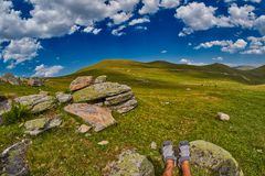 Tourist feet high-altitude abstract mountain landscape. With rocks and valleys in the background Stock Images