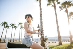 Tourist female taking a tour to exploring around town using electric bicycle. Tourist female wearing helmet taking a tour to exploring around small town with Royalty Free Stock Image
