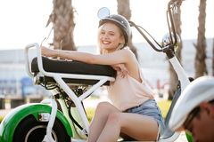 Tourist female taking a tour to exploring around town using electric bicycle. Tourist female wearing helmet taking a tour to exploring around small town with Stock Photo