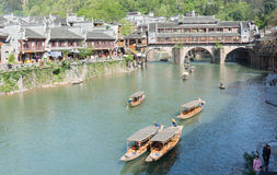 Tourist in Fenghuang,China. FENGHUANG - April 13:Wooden boats with tourists at Fenghuang ancient town on April 13, 2015 in Fenghuang,China.Fenghuang ancient Stock Photos