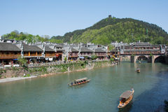 Tourist in Fenghuang Town,China. FENGHUANG - April 13:Wooden boats with tourists at Fenghuang ancient town on April 13, 2015 in Fenghuang,China.Fenghuang stock photo
