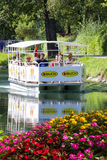 Tourist ferry boat crossing a river. Near lake Wörthersee. Klagenfurt, Austria. Tourist boat in a river. A tourist ferry crossing the river near Klagenfurt in Royalty Free Stock Photos