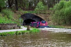 A tourist ferry boat enters a tunnel from Falkirk Wheel boat lift to Union Canal locks on the other side, Scotland Royalty Free Stock Photos